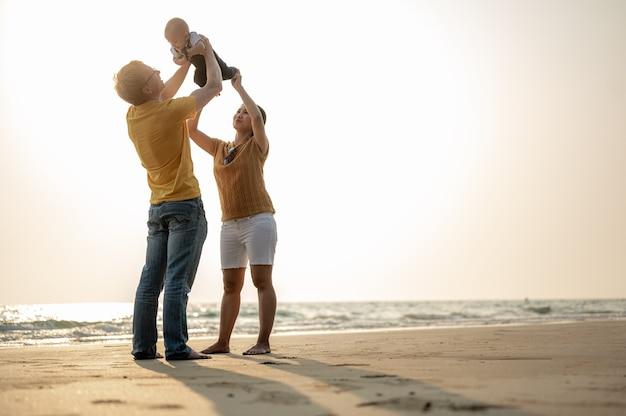 Buone vacanze in famiglia. madre gioiosa, padre, figlio piccolo camminano con divertimento lungo il bordo del tramonto sul mare e sulla spiaggia. vacanza in famiglia sulla spiaggia in estate, concetto di viaggio, vacanza e stile di vita