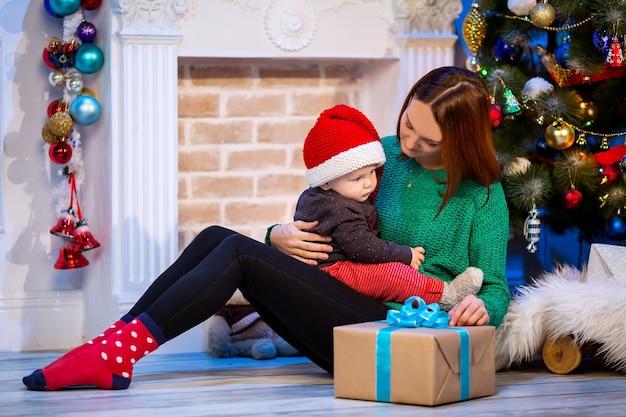 Famiglia felice all'interno di una casa sullo sfondo dell'albero di natale con regali