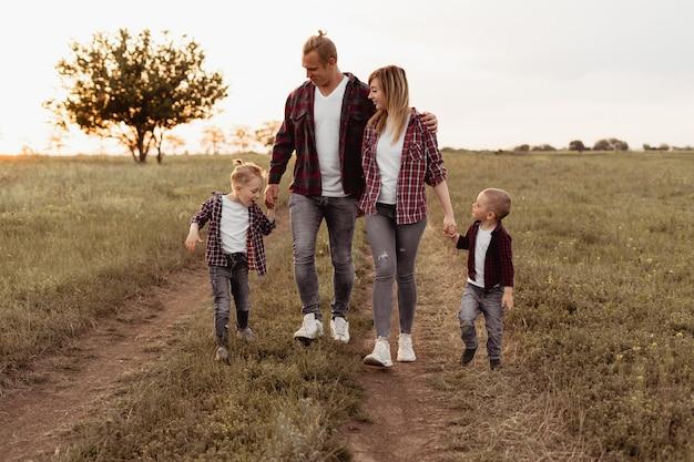 Una famiglia felice si diverte e cammina nel campo