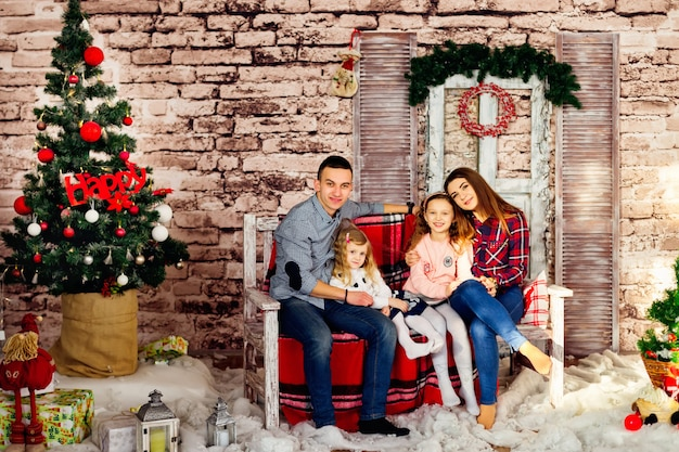 La famiglia felice è seduta su una panchina nello scenario delle vacanze
