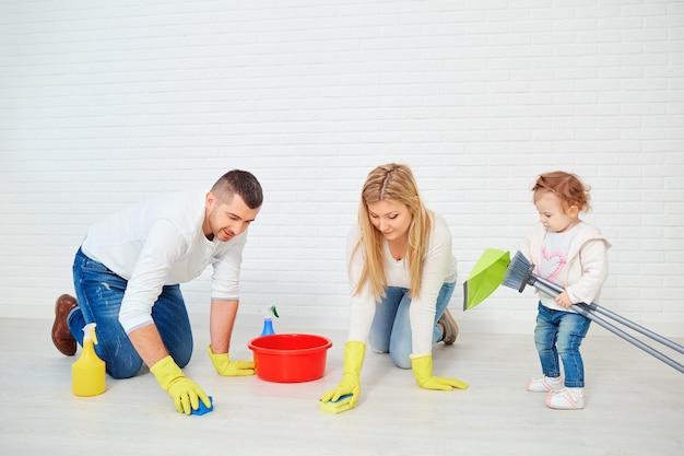 Una famiglia felice sta lavando il pavimento