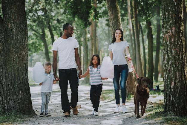 Proprietari di happy family e kids dog che camminano vicino al parco