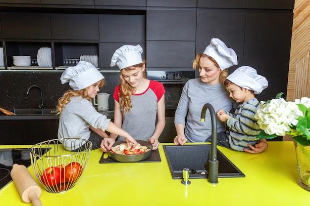 Famiglia felice in cucina. madre e tre bambini che preparano cuocere la torta di mele. mamma figlio e figlie che cucinano cibo sano a casa e si divertono. famiglia, aiuto nel lavoro di squadra, concetto di maternità