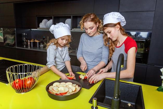 Famiglia felice in cucina. madre e due bambini che preparano l'impasto, cuociono la torta di mele. mamma e figlie che cucinano cibo sano a casa e si divertono. famiglia, aiuto nel lavoro di squadra, concetto di maternità