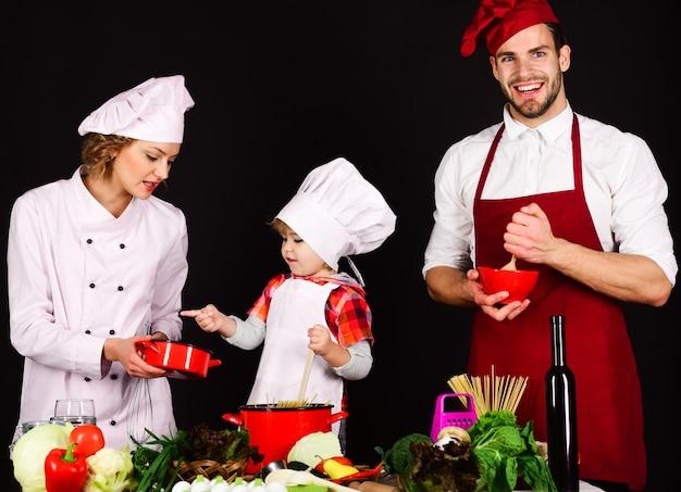 Famiglia felice in cucina. genitori con figlio che preparano la cena. cibo sano a casa. cibo fatto in casa.