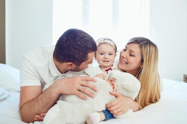 Famiglia felice sdraiato sul letto in camera da letto.