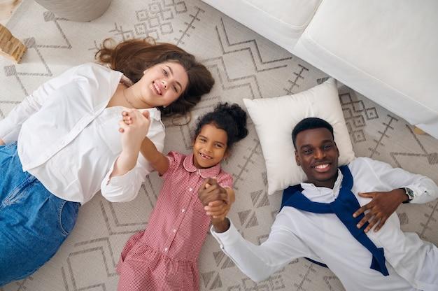 Famiglia felice sdraiata sul pavimento in soggiorno