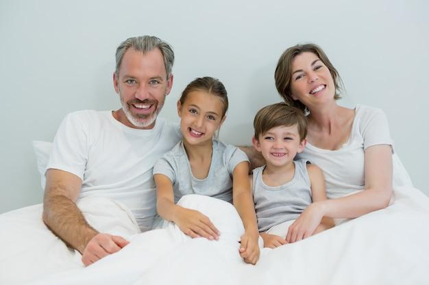 Famiglia felice che si trovano insieme sul letto in camera da letto a casa