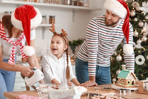 Famiglia felice che produce gustosi biscotti di panpepato in cucina alla vigilia di natale