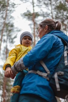 Famiglia felice mamma e bambino camminano insieme nella foresta dopo la pioggia con gli impermeabili, si abbracciano e si guardano l'un l'altro