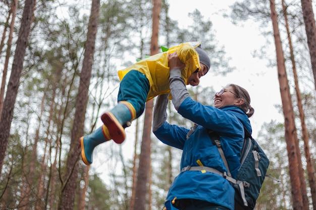 Famiglia felice mamma e bambino che camminano insieme nella foresta dopo la pioggia con gli impermeabili, la mamma lancia il bambino in cielo