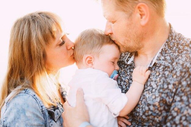 Famiglia felice - mamma e papà tengono in braccio un figlioletto e si baciano in riva al mare vicino al