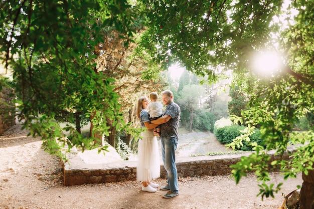Famiglia felice - mamma e papà tengono in braccio un figlioletto nel parco tra splendidi alberi
