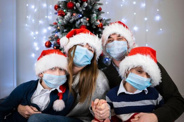 Famiglia felice, mamma papà e bambini in maschere protettive vicino a un bellissimo albero di natale.