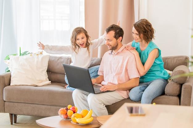 Famiglia felice, mamma, papà e figlia sono seduti sul divano e guardano insieme il monitor del laptop.