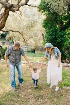 Famiglia felice - mamma e papà tengono il piccolo figlio per le braccia nell'oliveto