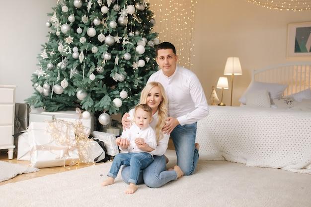 Famiglia felice di mamma, papà e figlioletto a casa nel periodo natalizio. momenti felici.