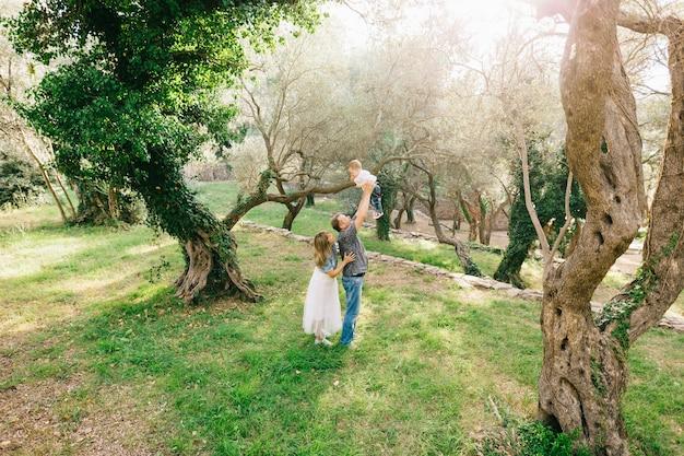 Famiglia felice - mamma, papà e figlioletto insieme nell'oliveto, papà solleva il bambino tra le sue braccia