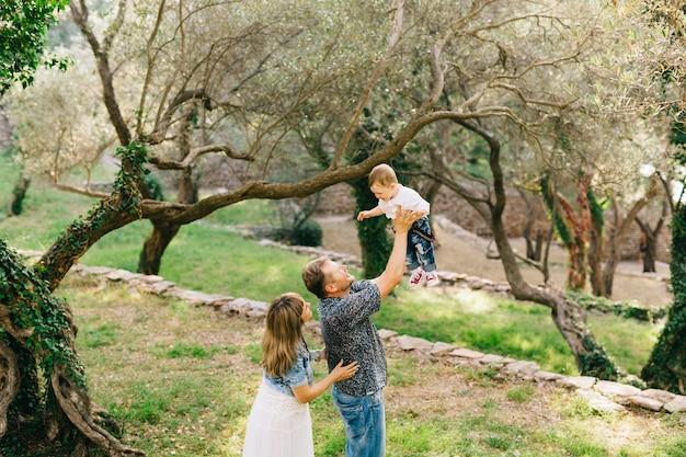 Famiglia felice - mamma, papà e figlioletto insieme nell'oliveto, papà solleva il bambino nel suo
