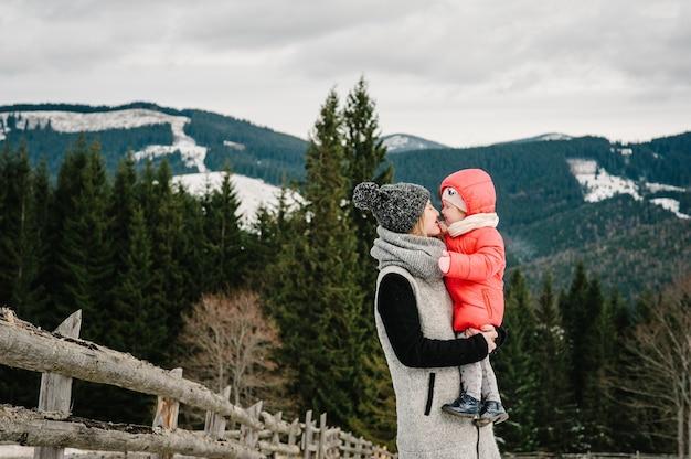 Famiglia felice: mamma e ragazza si divertono e giocano in inverno nevoso, camminano in montagna, natura. figlia di madre e figli che gode del viaggio frost stagione invernale.