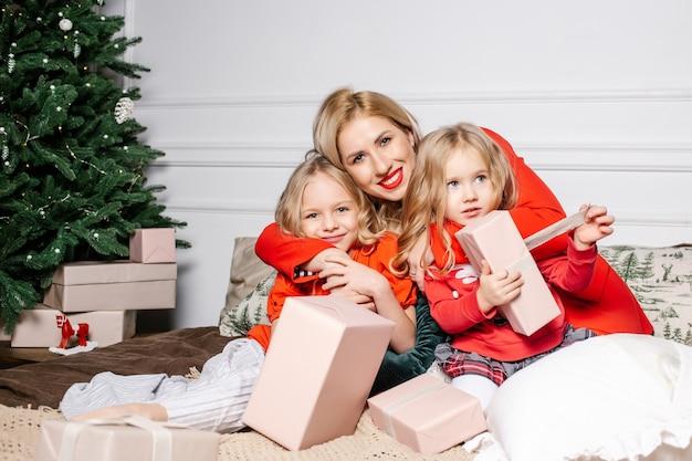 La mamma di famiglia felice abbraccia e regala la scatola dei regali alle sue figlie in una stanza con decorazioni natalizie a casa.