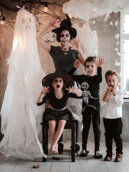 Famiglia felice mamma e bambini in costume e trucco alla celebrazione di halloween