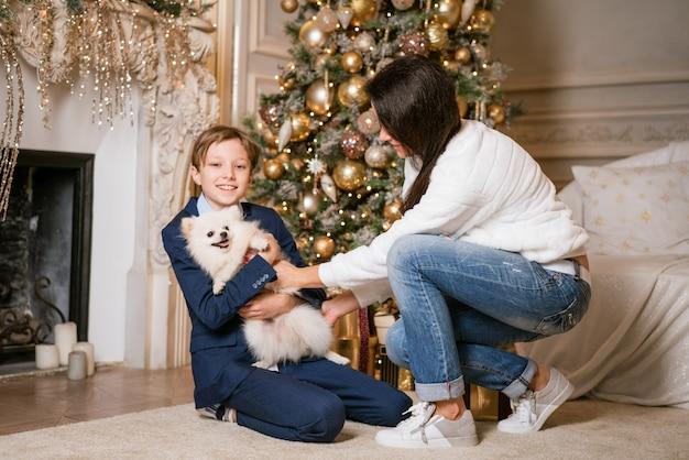 Famiglia felice mamma e figlio sono seduti vicino a un albero di natale con una donna cane con la famiglia a cri...