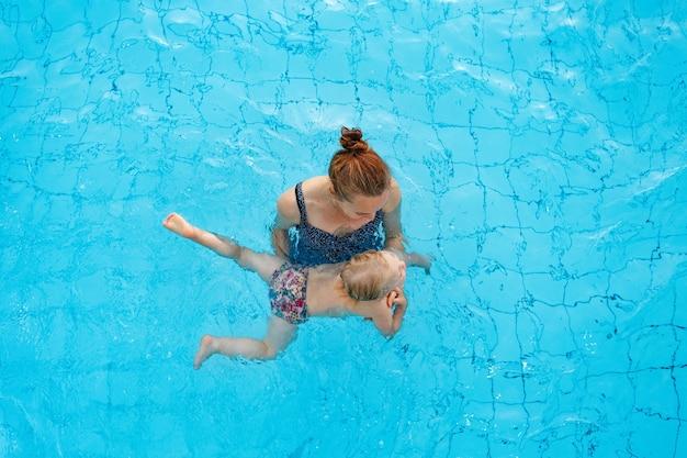 La mamma di famiglia felice insegna a sua figlia di anni a nuotare nella vista dall'alto della piscina