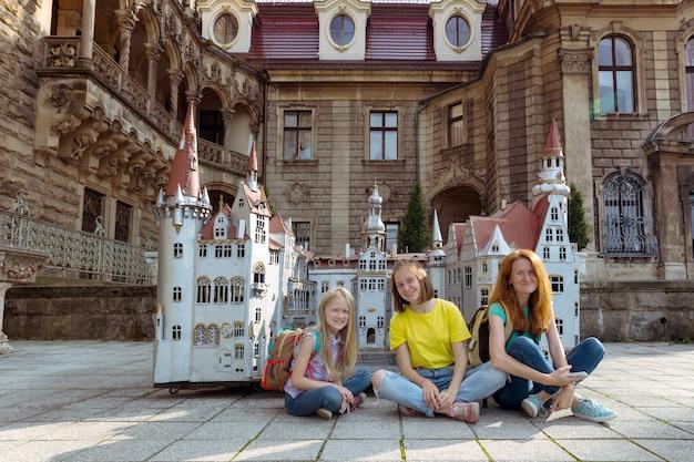 Famiglia felice - mamma e due figlie sono sedute in un prato bellissimo castello sullo sfondo