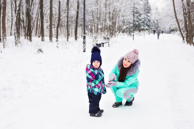 La madre e la figlia felici del bambino della famiglia su un inverno camminano nel bosco