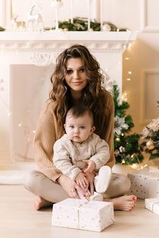 Madre di famiglia felice e figlia del bambino la mattina di natale presso l'albero di natale con i regali