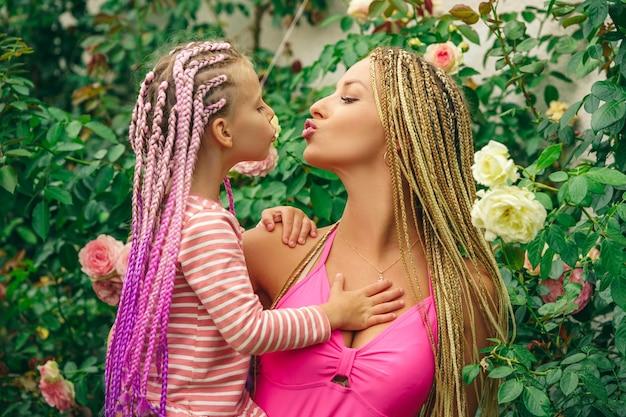Madre di famiglia felice e figlia del bambino che abbracciano e baciano madre felice che abbraccia il suo primo piano della figlia...