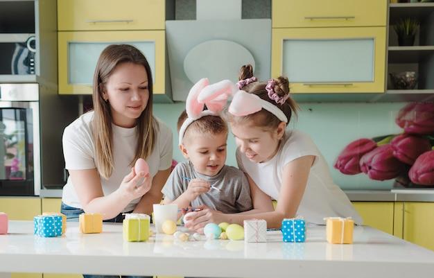 Famiglia felice: madre figlia e figlio con orecchie da coniglio si stanno preparando per le vacanze, colorando le uova nell'accogliente cucina di casa. preparativi per le vacanze di pasqua