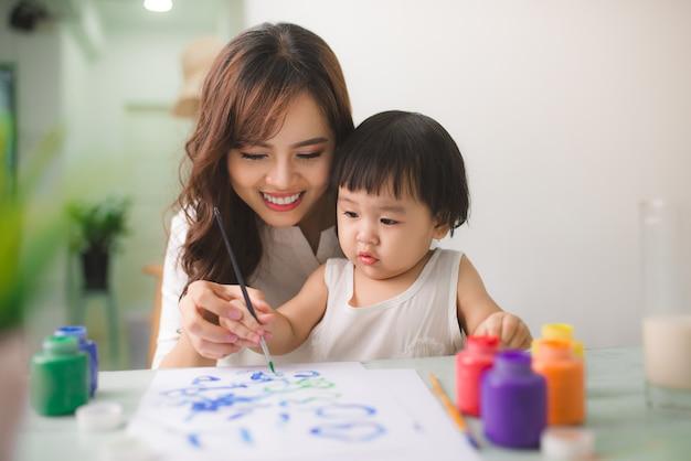 La madre e la figlia felici della famiglia dipingono insieme. la donna asiatica aiuta la sua bambina.