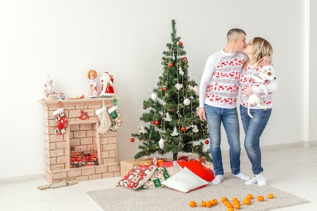 Famiglia felice madre padre e figlio a albero di natale a casa.