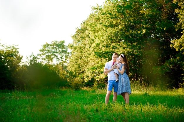 Famiglia felice: madre, padre e figlia nel parco al tramonto.