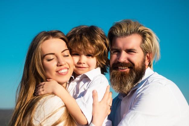 Abbraccio felice del figlio della famiglia, della madre, del padre e dei bambini. giovane famiglia sorridente con un bambino che si diverte insieme. i bambini amano e si abbracciano. faccia sorridente.