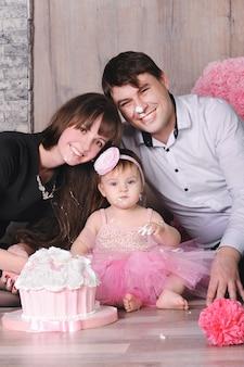 Famiglia felice - madre, padre e figlia che celebrano il primo compleanno con la torta.