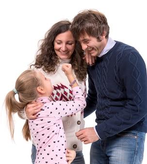 Famiglia felice. madre, padre e figlia in posa su un muro bianco