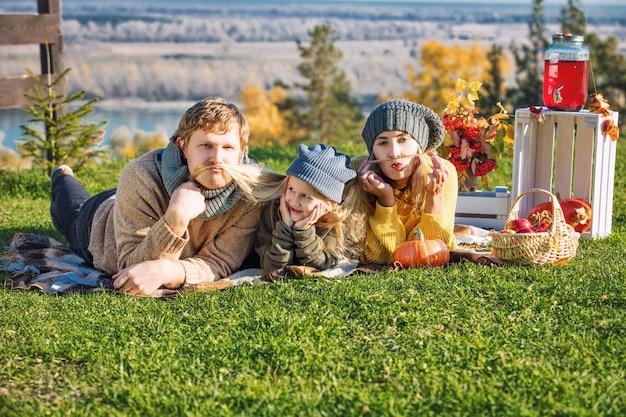 Felice madre di famiglia padre e figlia insieme in natura durante un picnic con zucche a quadri
