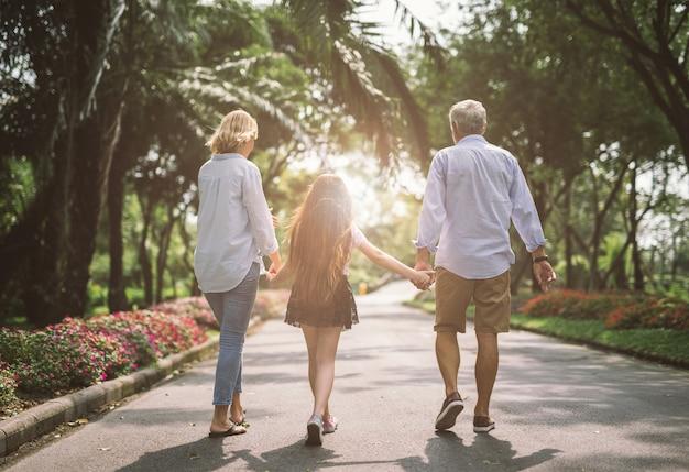 Il padre e la figlia felici della madre della famiglia camminano sulla natura sulla mano della tenuta del tramonto
