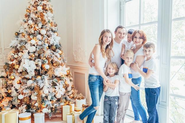 Felice madre di famiglia padre cinque figli si rilassano giocando vicino all'albero di natale alla vigilia di natale a casa. mamma papà figlia figlio in camera luminosa con decorazioni invernali. natale capodanno tempo di festa