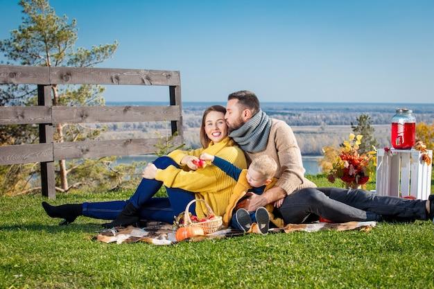 Felice madre di famiglia padre e figlio piccolo insieme in natura durante un picnic con zucche a quadri