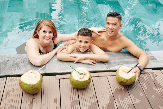 Famiglia felice di madre, padre e figlio preadolescente bevendo cocktail di cocco e rinfrescante in piscina