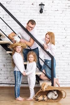 Felice madre di famiglia, padre, due figlie e conigli animali pelosi seduti a casa sulle scale