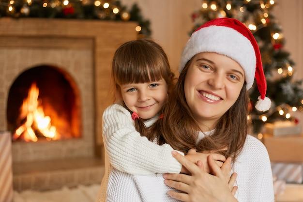 Madre di famiglia felice e piccolo bambino che giocano alla vigilia di natale, pongono in salotto, abbracciano e si divertono