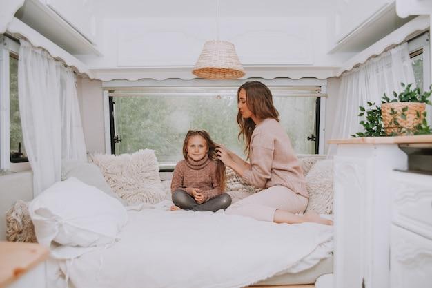 Famiglia felice - madre e figlia piccola che si rilassano nella campagna all'interno dell'interno rustico scandinavo bianco del camper.