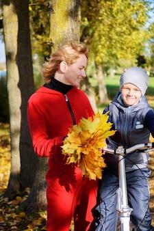 Madre e figlio di famiglia felici comunicano durante una passeggiata autunnale. la madre insegna a suo figlio ad andare in bicicletta.