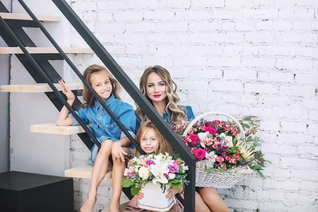 Madre di famiglia felice e due belle ragazze figlie in vacanza in fiori insieme in casa