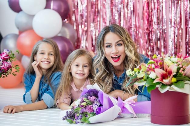 Madre di famiglia felice e due figlie di belle ragazze in vacanza insieme nei fiori